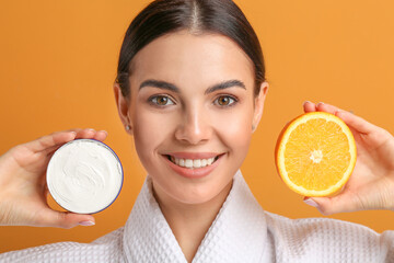 Fototapeta Beautiful young woman with orange and facial cream on color background obraz