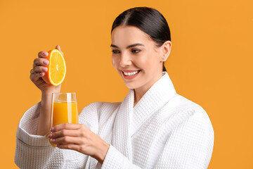 Fototapeta Beautiful young woman making fresh orange juice on color background obraz