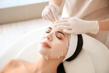 Fototapeta Cosmetologist applying sheet mask on woman's face in beauty salon obraz