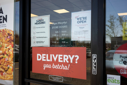 Tigard, OR, USA - Apr 16, 2021: Eye-catching delivery advertisement is seen next to enhanced safety measures signage at the entrance to a Papa Murphy's pizza restaurant in Tigard, Oregon.