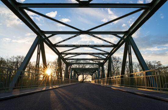Empty bridge over a railroad during a spring sunrise.