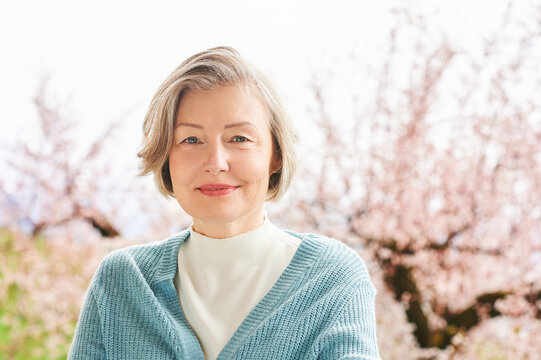 Spring portrait of beautiful and elegant middle age woman posing against pink blooming tree