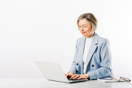 Studio portrait of middle age woman posing on white background, sitting at the desk, using laptop