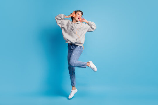 Full length photo portrait of woman jumping up with headphones isolated on pastel blue colored background