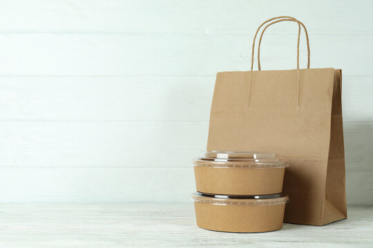 Paper bowls and paper bag on white wooden table