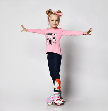 cute blonde girl in a pink sweater with a print of kittens and legends with a picture of roller skating, she spread her arms to the sides for balance