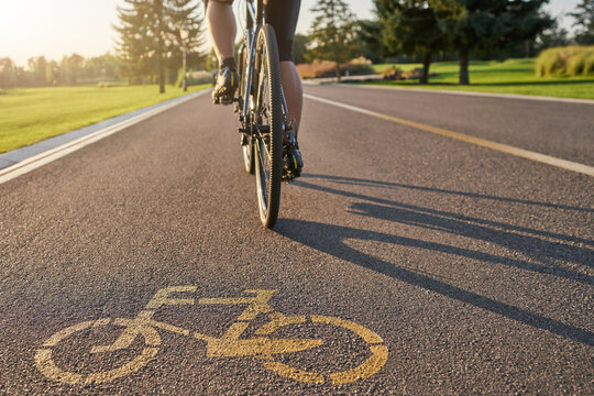 Place to train. Close up of a bicycle sign drawn on asphalt. Professional male cyclist riding a road bike on a cycle path
