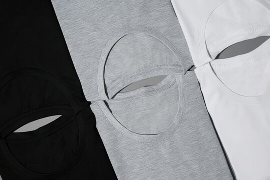Top view of folded monochrome t shirts black, gray and white lying diagonally isolated on gray surface