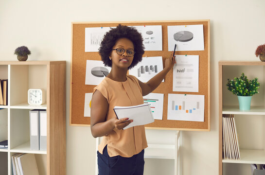 Young business lady, mentor or company marketing manager making presentation using financial data materials pinned on office bulletin board, training employees, explaining strategy, sharing expertise