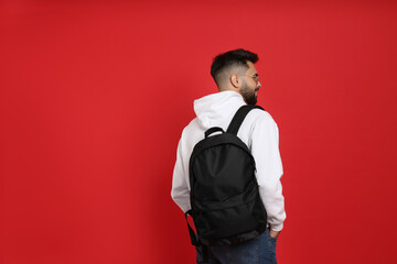 Young man with stylish backpack on red background, back view. Space for text