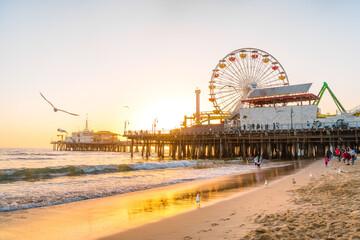 Santa Monica Pier on the background of an orange sunset, calm ocean waves, Los Angeles, California