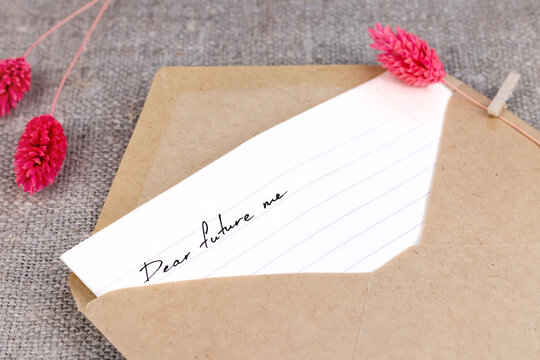 """Letter to the future: """"dear future me"""" is written on lined paper, in a craft envelope. Dry pink flowers lie nearby, one flower attached to the letter with wooden clothespin"""