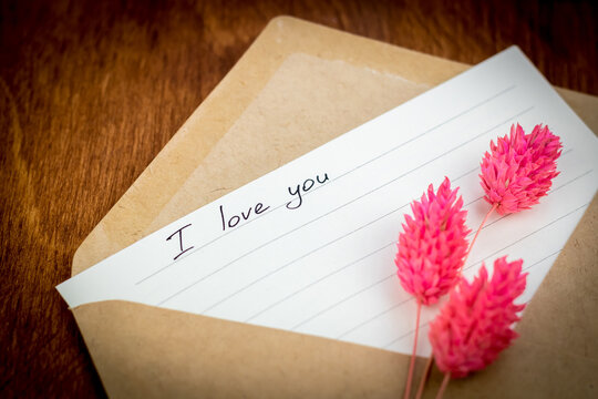 """Declaration of love in a letter: the phrase """"I love you"""" on lined paper in a craft envelope. Near pink dried flowers"""