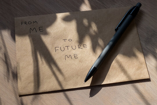 Craft envelope and pencil in the rays of sun and the shadows of plants. A letter to the future, is written on the envelope: from me to future me