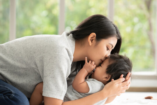 Young beautiful aisan mother kissing her baby.