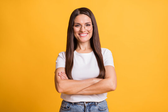 Photo of confident happy woman wear glasses crossed hands beaming smile isolated on yellow color background