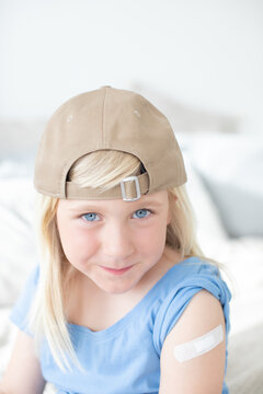 Laughing, cute, blond child, girl, boy, looking happy and proud to the camera, he has a band-aid on his upper arm.