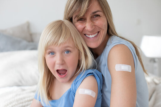 Mother and daughter look happily laughing, both into the camera and wear their plasters on their upper arms after the injection or vaccination and are satisfied.