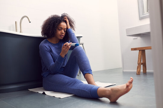 Disappointed Woman Sitting On Floor In Bathroom At Home With Negative Home Pregnancy Test