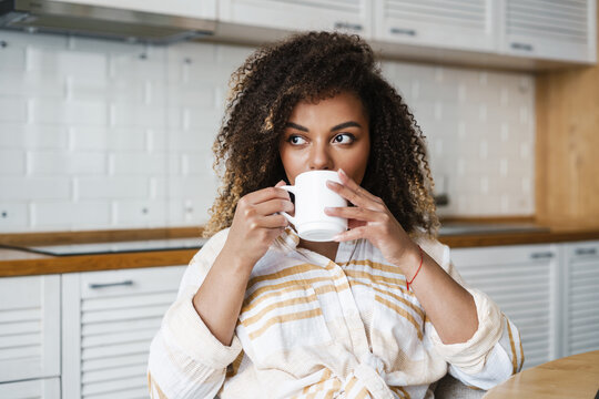 The happy woman drinking something from a cup and looking to the side while sitting at the table in the kitchen