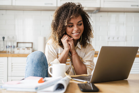 The smiling black woman in a wired headphones touching her hands to her face while sitting in front of a laptop in the kitchen