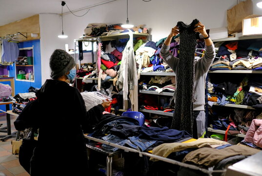 Volunteers offer donations of clothes for people at Sant Pau gym, one day before the gym is evicted from the building by court order, in Barcelona