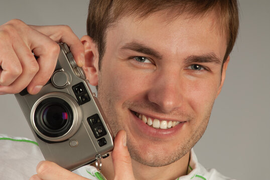 young man with a camera in his hands smiles and looks at the camera, close-up.