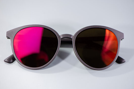 Dark sunglasses and orange and red reflections in glasses lie on a light background.