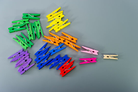 Conceptual composition, where multi-colored wooden clothespins are arranged in groups on a gray background.