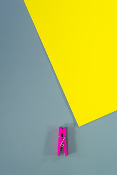 Conceptual composition, a yellow paper sheet and a fuchsia wooden clothespin on a gray background.