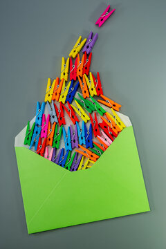 Conceptual composition, open green envelope and multi-colored clothespins on a gray background.
