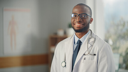 Close Up Portrait of Happy African American Family Medical Doctor in Glasses in Health Clinic. Successful Black Physician in White Lab Coat Looks at the Camera and Smiles in Hospital Office.