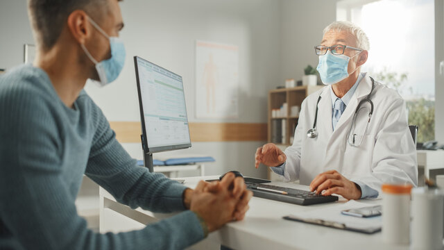 Middle Aged Family Doctor is Talking with Young Male Patient During Consultation in a Health Clinic. Both Wear Face Masks. Physician in Lab Coat Sitting Behind a Computer Desk in Hospital Office.