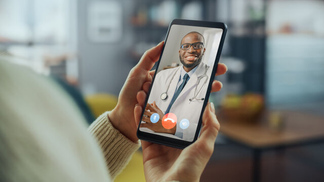 Close Up of a Female Has a Video Call with Her Female Family Doctor on Smartphone from Living Room. Ill-Feeling Woman Making a Call from Home with Physician Over the Internet.