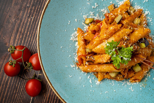 Penne pasta in tomato sauce, tomatoes decorated with parsley on a wooden background