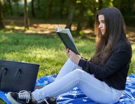 beautiful long-haired woman reading a green book in nature sitting on the grass with a blanket and her bag with trees in the background. teenager looking at a literary work in the park smiling