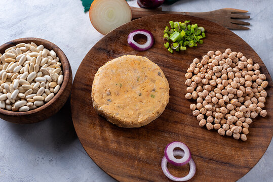 Vegan and vegetarian burgers made of very healthy assorted legumes and fresh vegetables on a wooden plate and gray countertop.