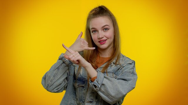 Call me, here is contact number. Cheerful cute girl in denim jacket looking at camera doing phone gesture like says hey you call me back. Young woman posing isolated on yellow studio wall background