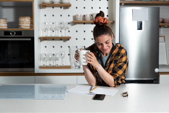 Young freelancer woman wedding planner stands in the kitchen drinking coffee from a cup and coming up with new ideas for clients as she reads what she has written down from the options in her diary