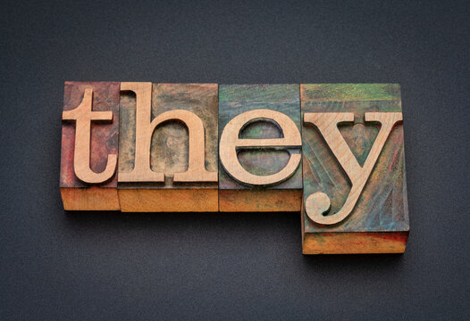 they - word abstract in vintage letterpress wood type against black matte background