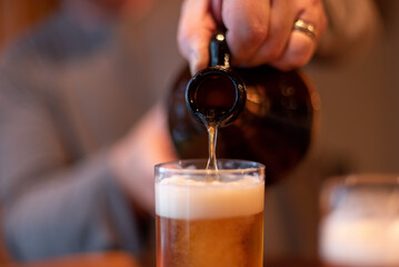 Closeup of craft beer being poured from a growler