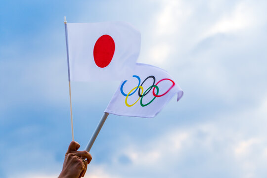 Fan waving the national flag of Japan and the Olympic flag with symbol olympics rings.