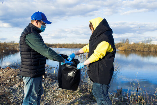 volunteers collect plastic bottles in bags on the river bank, the concept of ecology and land protection