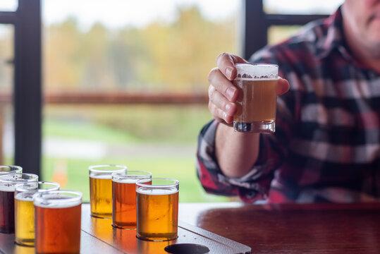 Man at a restaurant sampling beer from a beer flight