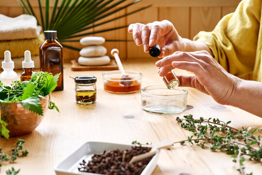 Woman prepares aromatherapy session at the table with essential oil diffuser medical herbs, different types of oils and essences. Aromatherapy and alternative medicine concept. Natural remedies.