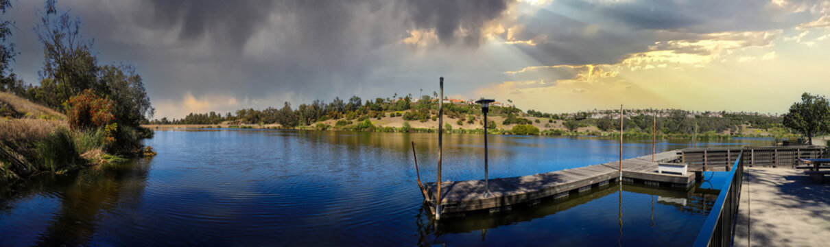 a stunning panoramic shot of vast still blue lake water and mountain ranges filled with lush green plants and trees and luxury homes with an old wooden dock on the lake at Laguna Niguel Regional Park