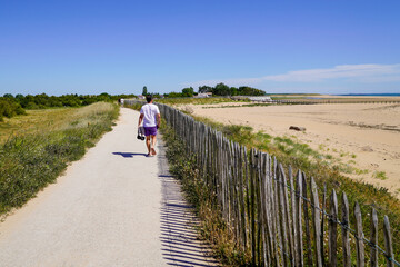 tourist man walking in summer day aside sand beach in Jard-sur-Mer France