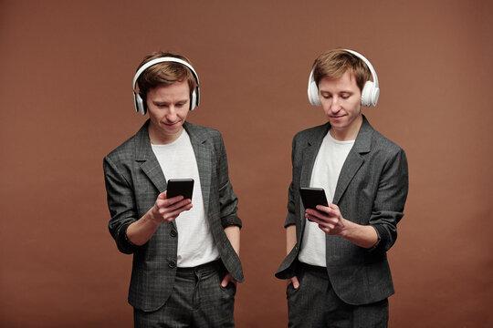 Tweens in suits enjoying music in headphones