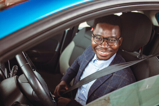 Young happy man fastening his seatbelt before a trip by car and looking at camera. Portrait of young hispanic man sitting in driving seat of car, fastening safety belt and making en eye contact