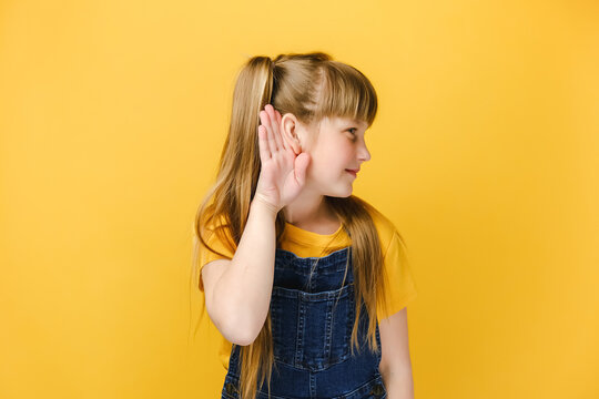 Curious little girl kid likes gossips, wants to overhear secret information, tries to hear conversation, listens attentively keeps hand near ear for eavesdropping, isolated on yellow studio background